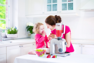 laughing girl and her young mother making fresh strawberry fruit juice for breakfast